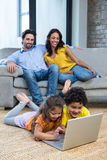 Children laying on carpet in living room using laptop. While parents on the sofa Royalty Free Stock Photo