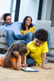 Children laying on the carpet using tablet in living room. While parents on sofa using laptop Stock Photo