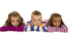 Children laying down wearing pajamas looking at camera Royalty Free Stock Photo