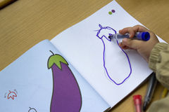 Child learn to draw. Is drawing eggplant stock photo