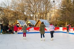 Children learn to skate on the open-air ice rink. Winter sports and seasonal fun during Christmas and New Year holidays stock photos