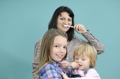Children learning brushing teeth. White child and teenager studying brushing tooth and mother teaching Royalty Free Stock Images