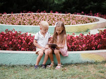 Children learning a digital tablet and sitting in the park. A boy and girl playing in a gadget on a natural background. Full-length photo of two handsome Royalty Free Stock Image