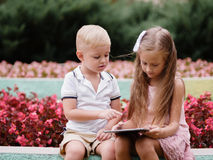 Children learning a digital tablet and sitting in the park. A boy and girl playing in a gadget on a natural background. A photo of two handsome children with a Stock Photo