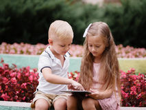 Children learning a digital tablet and sitting in the park. A boy and girl playing in a gadget on a natural background. stock photo