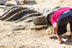 Children learning about, Excavating dinosaur fossils simulation royalty free stock image