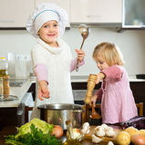 Children learning how to cook. Happy smiling children are learning how to cook in the kitchen Royalty Free Stock Photo