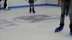 Children learning how to ice skate in a recreation hall stock footage