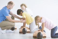 Children learning on manikins. Multiethnic group of children learning on manikins how to give first aid during training with a lifeguard Royalty Free Stock Photo
