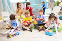Children learning musical instruments on lesson in kindergarten or preschool. Kids learning musical instruments on lesson in kindergarten or preschool royalty free stock photos