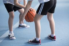 Children learning to dribble basketball. Close-up on young children wearing school sportswear learning to dribble a basketball during physical education classes stock image