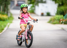 Children learning to drive a bicycle on a driveway outside. Stock Photography