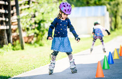 Children learning to roller skate on the road with cones. Stock Image