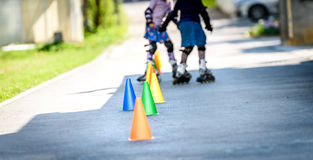 Children learning to roller skate on the road with cones. Stock Photos