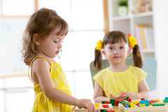 Children learning to sort shapes in kindergarten or daycare center. Children learning to sort shapes in kindergarten, home or daycare center royalty free stock photos