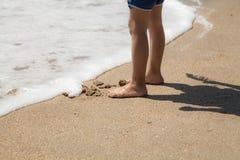 Children legs on the sea beach Royalty Free Stock Image