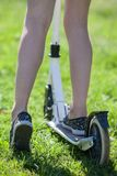 Children legs standing push-bicycle and green sunny grass, rear close-up view Stock Photography