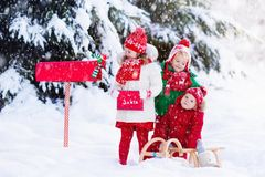 Children with letter to Santa at Christmas mail box in snow Stock Image