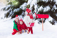 Children with letter to Santa at Christmas mail box in snow. Happy children in knitted reindeer hat and scarf holding letter to Santa with Christmas presents Stock Photo