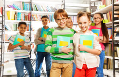 Children in library hold exercise books and stand Royalty Free Stock Photography
