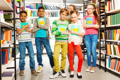 Children in library holding exercise books Royalty Free Stock Photo