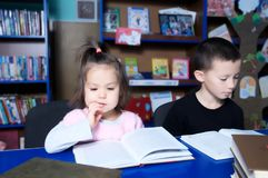 Children in library interesting reading book. Little girl and boy learning. Children in library interesting reading book. Little girl and boy together learning stock photography
