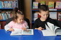 Children in library reading interesting book. Little girl and boy learning. Children in library reading interesting book. Little girl and boy together learning stock photo