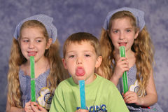 Children licking popsicles. Shot of three young children licking popsicles Royalty Free Stock Photography