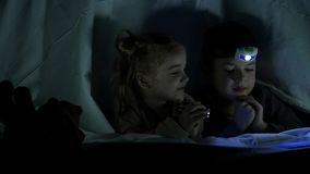 Children lie on the bed under the blanket, in their hands they have flashlights, they laugh. Slow motion