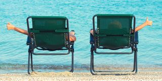Children lie on chaise longue and look at the sea. Children lie on chaise longue royalty free stock image