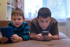 Children lie on the couch and play in smartphones royalty free stock photos