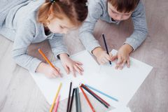 Children lie on the floor in pajamas and draw with pencils. Cute child painting by pencils.Hand of child girl and boy. Draw and paint with crayon. Close up view Stock Photography
