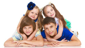 Children lie in four. Horizontally elongated rectangular frame. Two little girls sisters lie on top of his brothers and hugging them around the neck. The picture Royalty Free Stock Photos