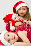 Children lie on fur in the hats of Santa Claus Royalty Free Stock Photography