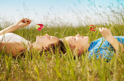 Sweet summer. Children lie on a grass and eat sweet sugar candies stock photography