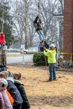 Children are lifted into the air by tree workers. March 17, 2019 New Carlisle Indiana USA; children are lifted into the air by tree workers while a line of royalty free stock photos