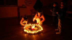 Children lighting candles in circle Royalty Free Stock Image