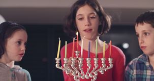 Children lighting Hanukka candles at home. Children lighting colorful Hanukka candles at home stock footage