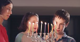Children lighting Hanukka candles at home. Children lighting colorful Hanukka candles at home stock video