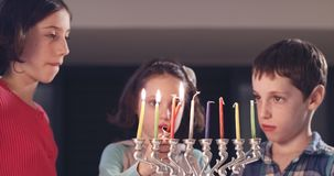 Children lighting Hanukka candles at home. Children lighting colorful Hanukka candles at home stock video footage