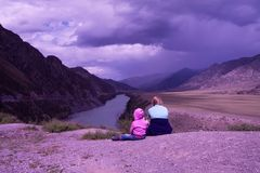 Children in lilac clothes sit in mountains under the cloudy vio Stock Photography