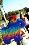 Children lined up for a hit of the pinata at a party. A colourful pinata sits in the foreground of the image while children line up behind it, awaiting their Royalty Free Stock Photography