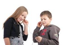 Children listen to music. On a white background Stock Photos