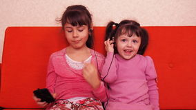 Children listen to music on headphones from a mobile phone. Two sisters listen to music on headphones. stock footage