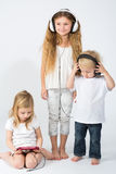 Children are listening to music on headphones and girl playing Royalty Free Stock Image