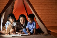Interesting book. Children listening to their mother reading an interesting story stock image