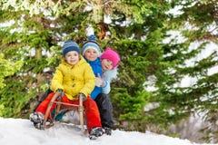 Children little boys and girl slide on sledge Royalty Free Stock Photos