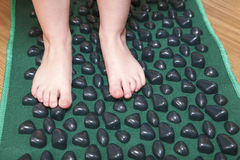 Children little feet standing on massage mat. For flatfoot treatment Stock Images