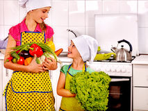 Children little girl cooking vegetables at kitchen. Children little girl cooking vegetable on their own at kitchen. Children keeps vegetable are kitchen Royalty Free Stock Images