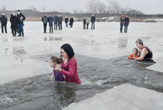 Children, little girls with adults swimming in the river in the winter Christian holiday Epiphany Stock Photo